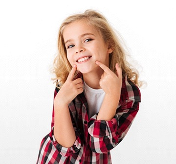 A young girl pointing at her smile