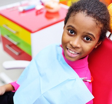 A young girl in the dentist chair smiling