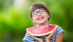 Smiling girl holding a watermelon slice