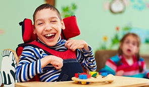 Laughing young boy in wheel chair