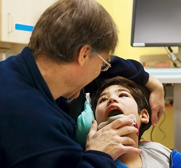 Dentist examining young boy's smile