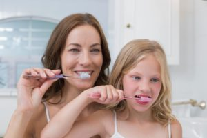 mom and daughter brushing together