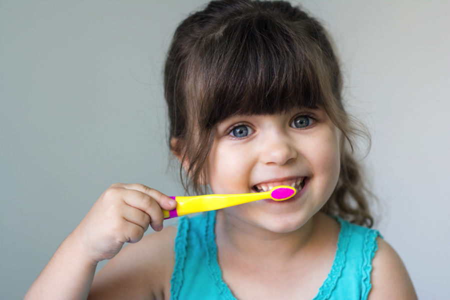 A little girl brushing her teeth on the advice of a pediatric dentist